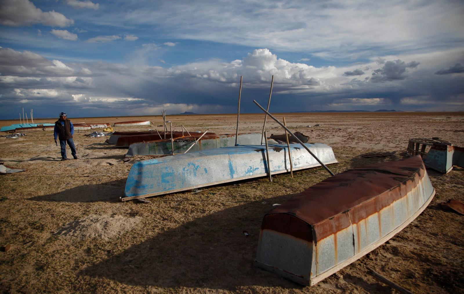 En fisker går forbi flere forlatte båter som en gang ble brukt til å fiske med.