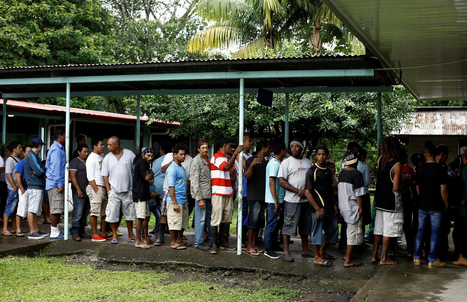 Lange køar med folk som ventar på å få mat ved eit evakueringssenter i Guapiles i Costa Rica.