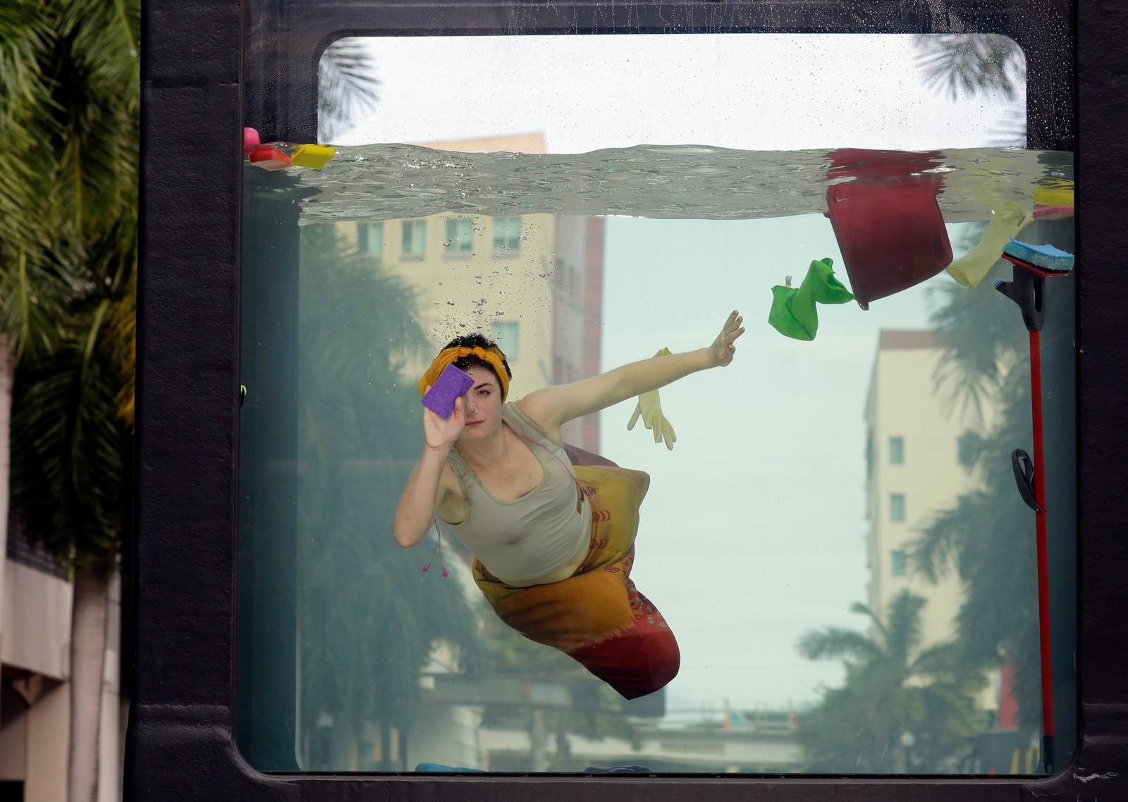 Performance-kunstneren Annie Saunders vasker vinduene mens vannet stiger. Installasjonen er en del av kunstuka i Miami, og er ment som en kommentar til klimaforandringene.