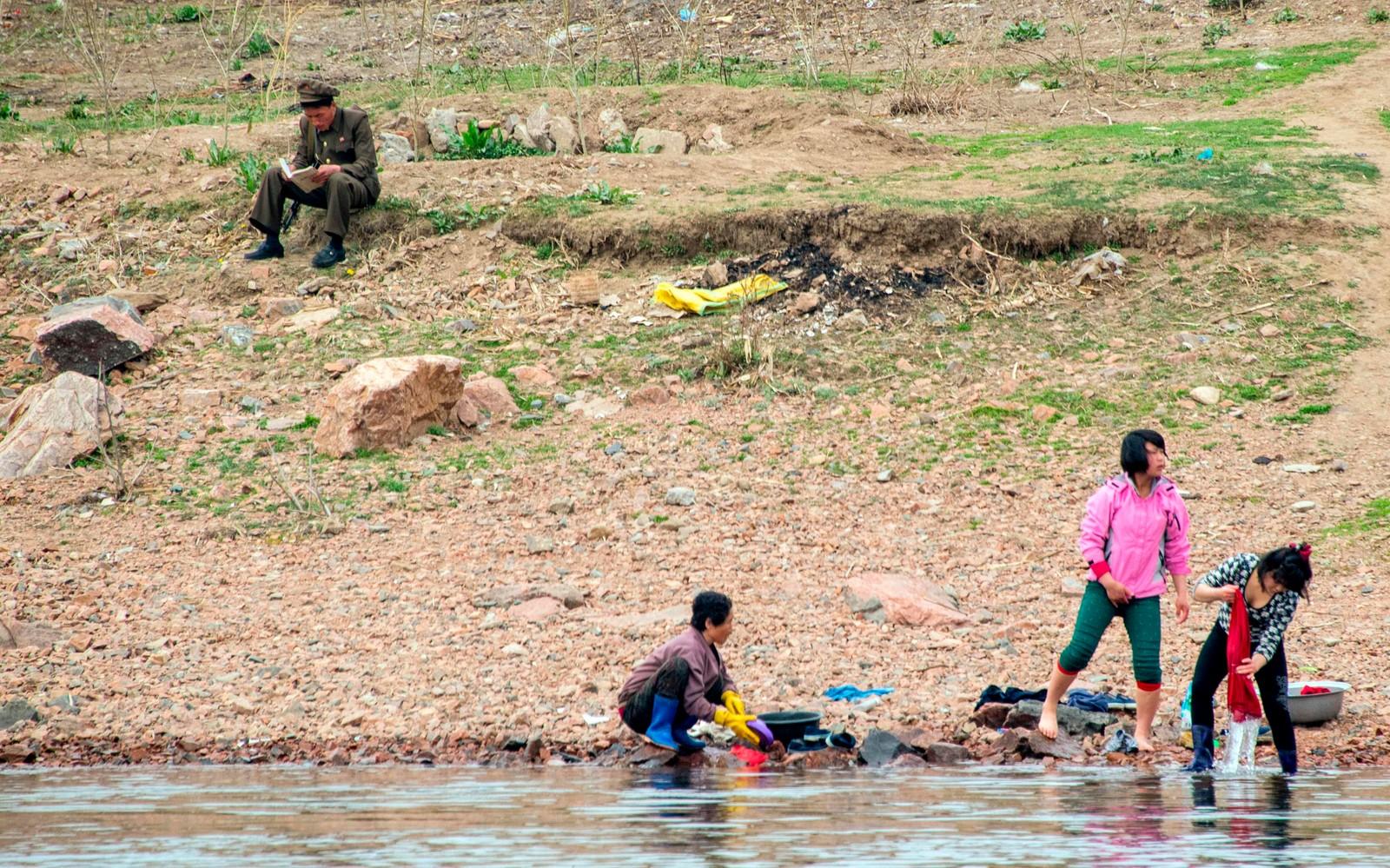Nordkoreanere vasker klær i elva Yalu ved grensen mot Kina.