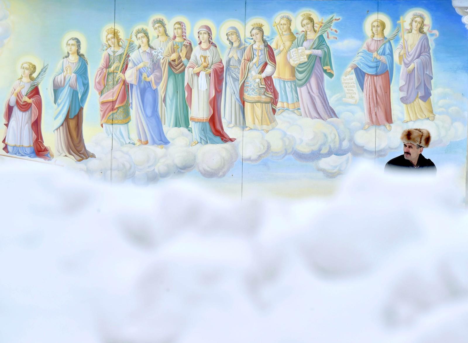 En mann står ved en freske etter massivt snøvær i Kiev i Ukraina.