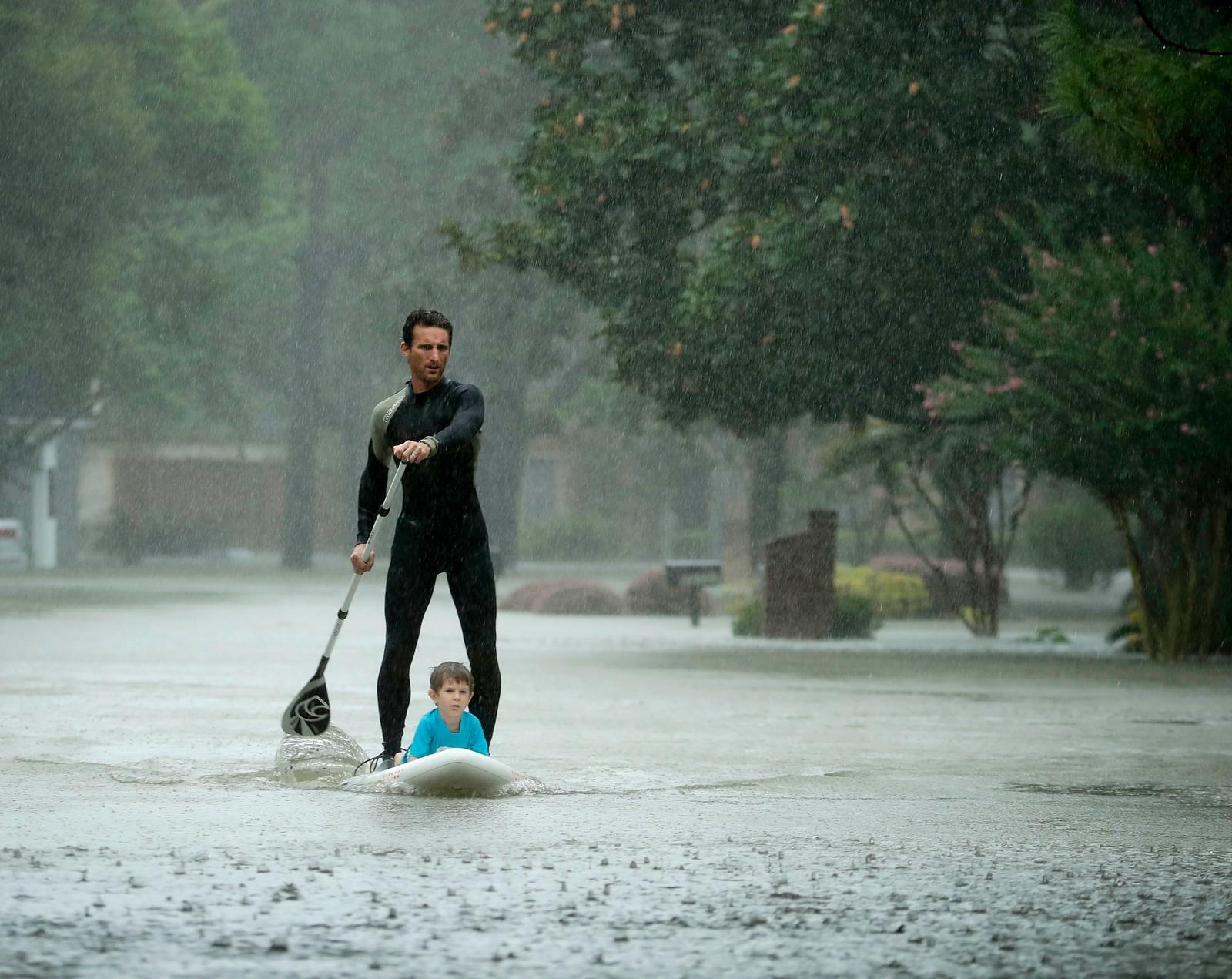Orkanen Harvey har ført til store flommer i Houston i Texas. Alexendre Jorge evakuerer fire år gamle Ethan Colman.