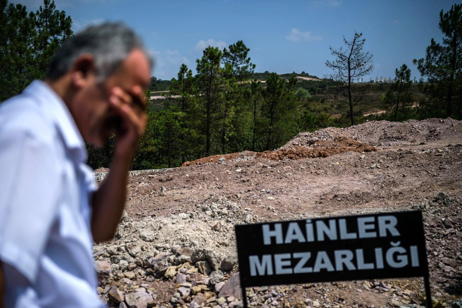 """En mann står ved siden av et skilt hvor det står """"forrædernes gravplass"""" i Istanbul i Tyrkia 28. juli. Gravene er ikke merket, og gravplassen er for soldatene som deltok i det mislykkede kuppet."""