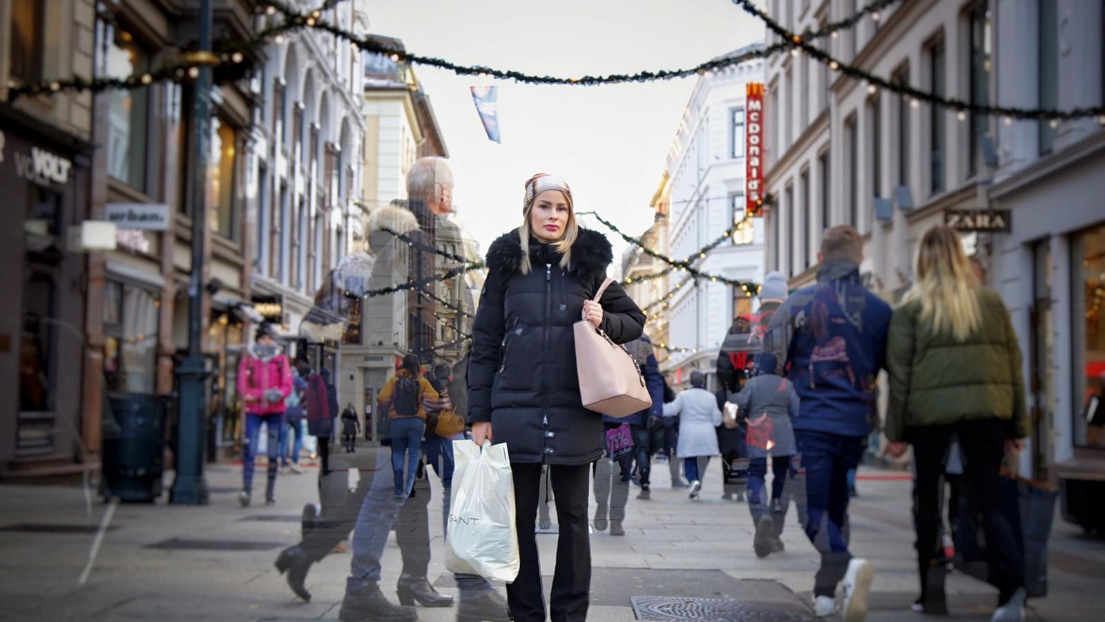 Ung kvinne med handleposer står midt på Karl Johans gate i Oslo og  folk haster forbi henne på begge sider. Vinter.