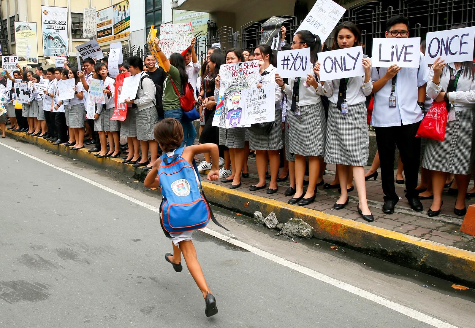 """YOLO. En jente løper foran studenter som demonstrerer mot president Rodrigo Dutertes kampanje mot narkotika. Presidenten har uttalt at han """"med glede vil slakte 3 millioner avhengige."""" Duterte har sammenlignet sin kamp mot narkotikaavhengige med Hitlers jødeforfølgelse. Bildet er tatt i Manila på Filippinene."""