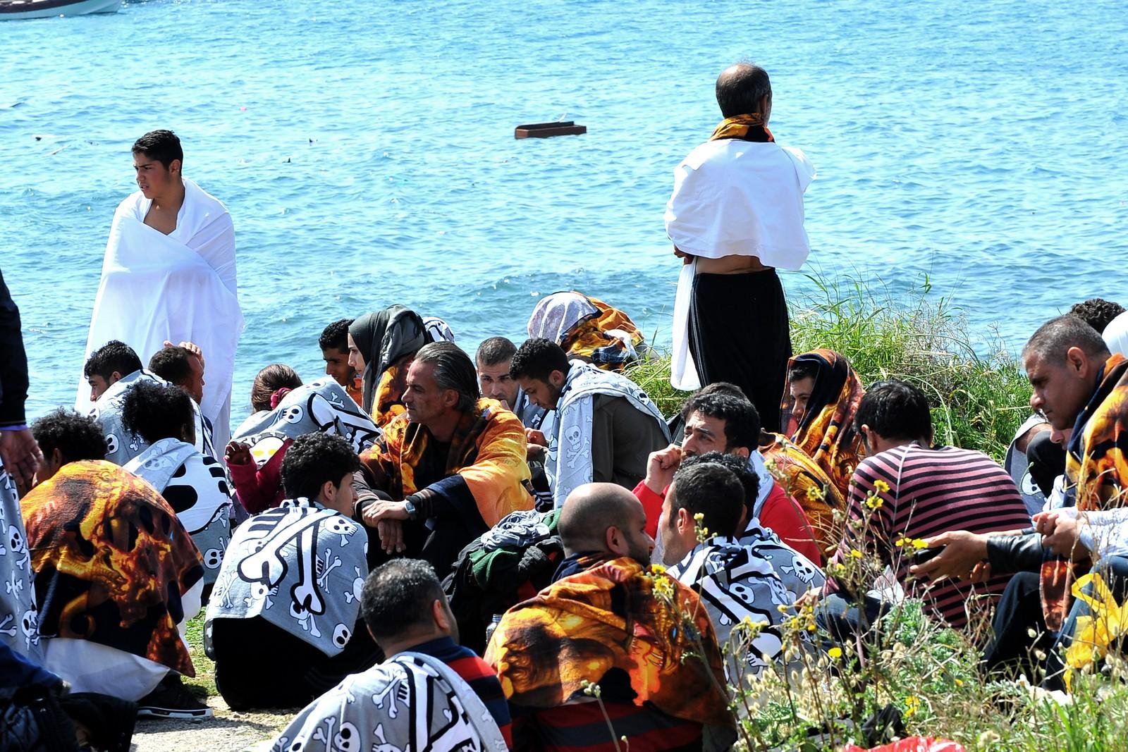Iført strandhåndklær venter båtflyktningene som reddet livet, på hva som skal skje med dem. Rhodos 20. april 2015.