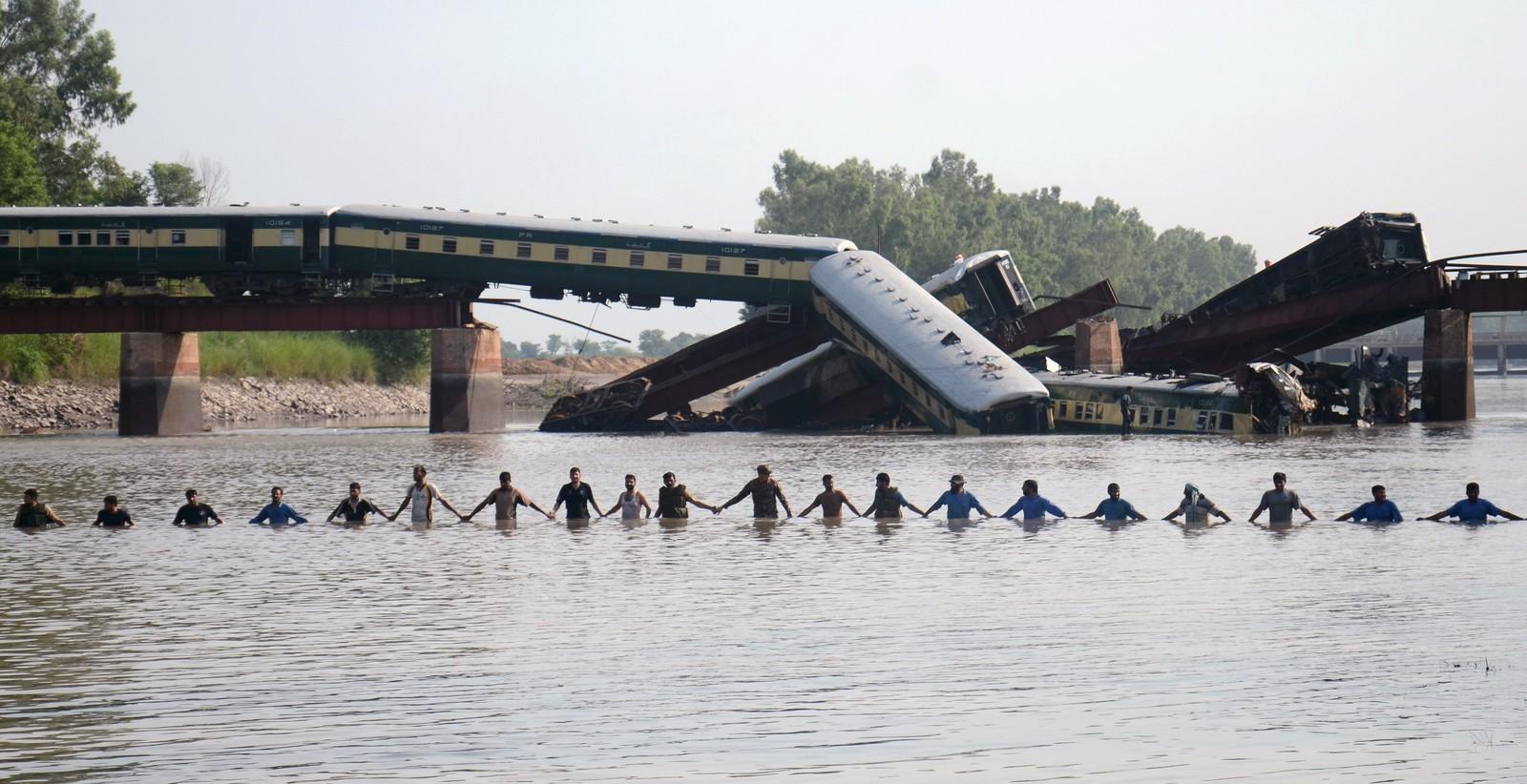 Pakistanske soldater holder hender under leteaksjonen etter at et tog kjørte ut og havnet i kanalen nær Gujranwala 3. juli. 19 personer døde og over 100 ble skadd i ulykken.