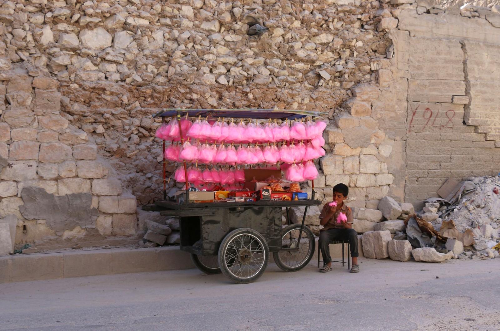 En syrisk gutt som selger sukkerspinn forsyner seg av varene i al-Bab.