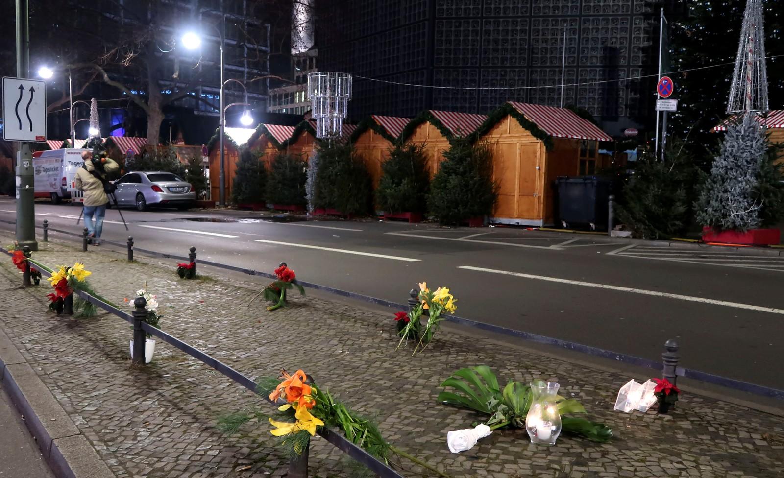 Folk har tent lys og lagt ned blomster utenfor julemarkedet.