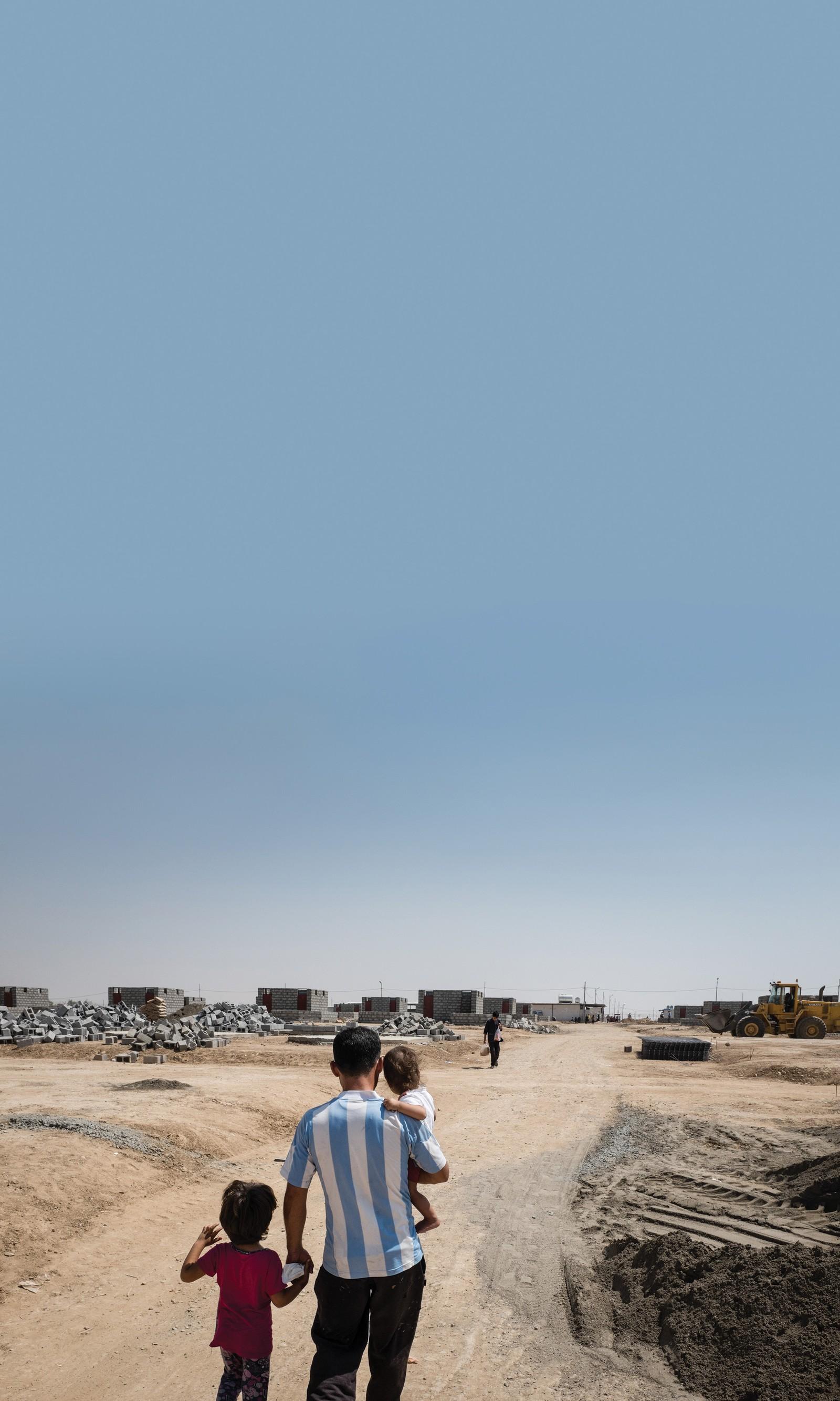 En syrisk mann på veg med sine døtre til en liten butikk han har bygd inne i Qushtapa-flyktningleiren i Erbil, som ligger i den kurdiske regionen i Irak.
