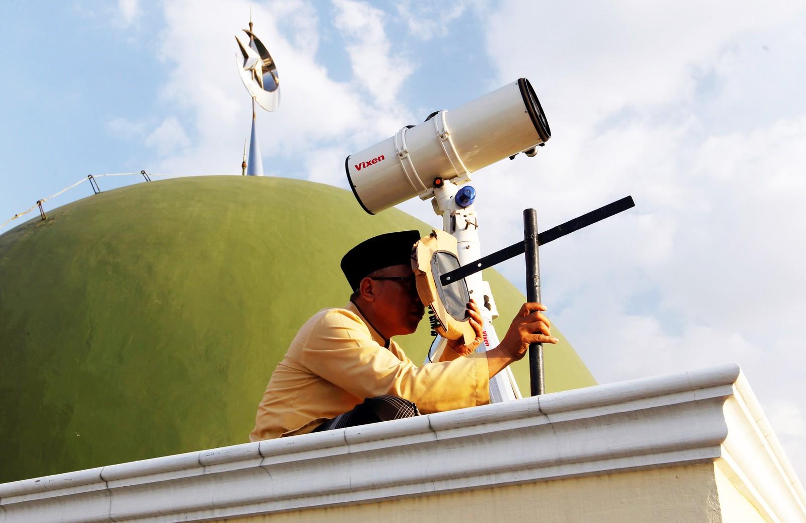 JAKARTA:En mann med teleskop sjekker månens posisjon fra taket på Al-Musyari'in-moskeen i Jakarta i Indonesia.