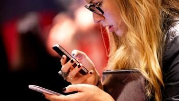 En kvinne sjekker mobiltelefonen sin i New York City
