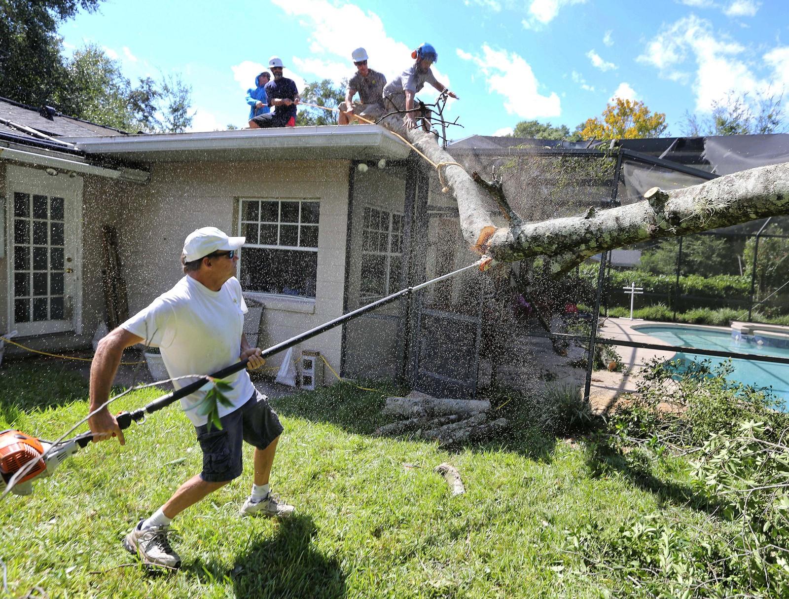 Tim Muench rydder opp i en hage i Maitland, Florida, søndag.