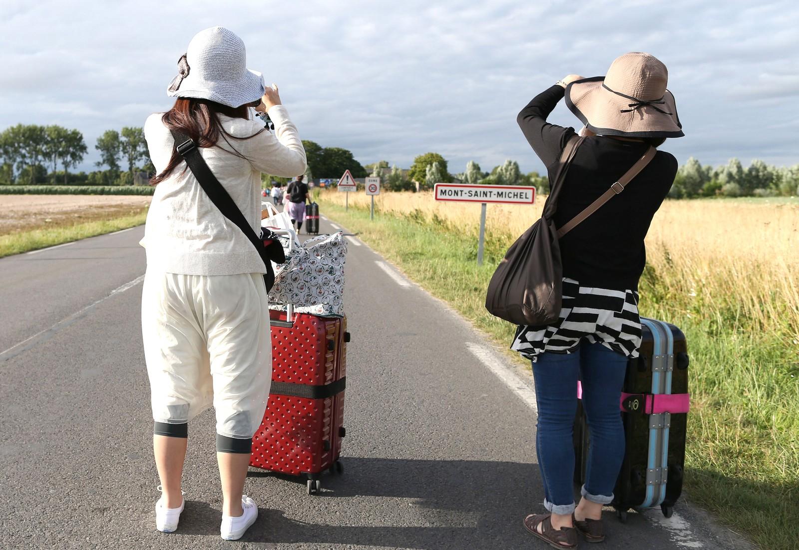 Det var ikke helt slik de hadde sett for seg ankomsten til feriestedet sitt. Disse turistene måtte ta beina fatt den siste delen av veien mot hotellet da bussen ikke kom forbi streikende, franske bønder i Mont Saint-Michel.  Hundrevis av sinte, franske bønder har blokkert veier og demonstrert i flere dager. De krever høyere kjøtt- og melkepriser.