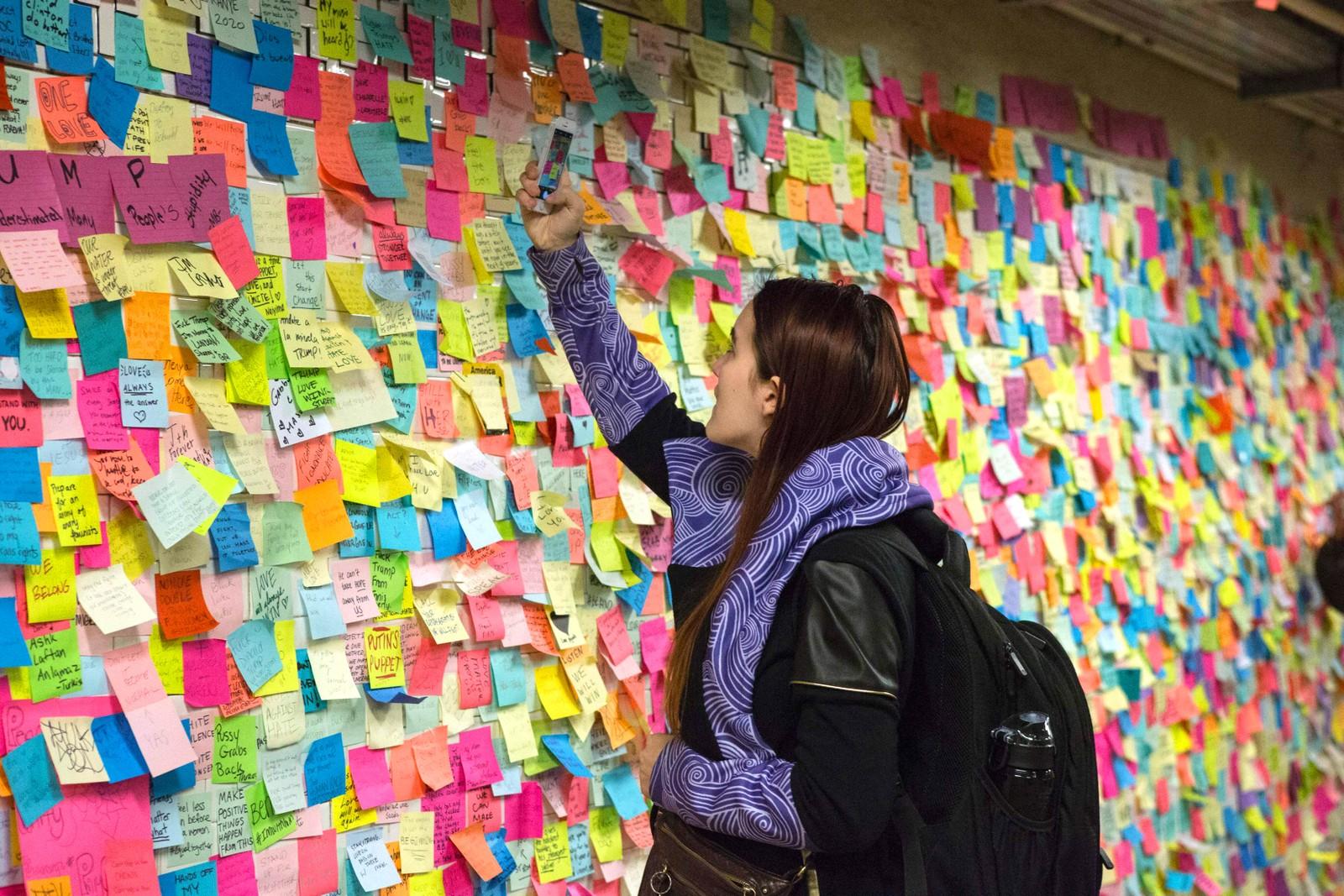 En kvinne klistrer en lapp på kunstverket 'Subway Therapy' på T-banestasjonen i Union Square i New York. Installasjonen så sitt lys dagen etter Donald Trump ble valgt til president. Folk oppfordres til å dele tanker og følelser.