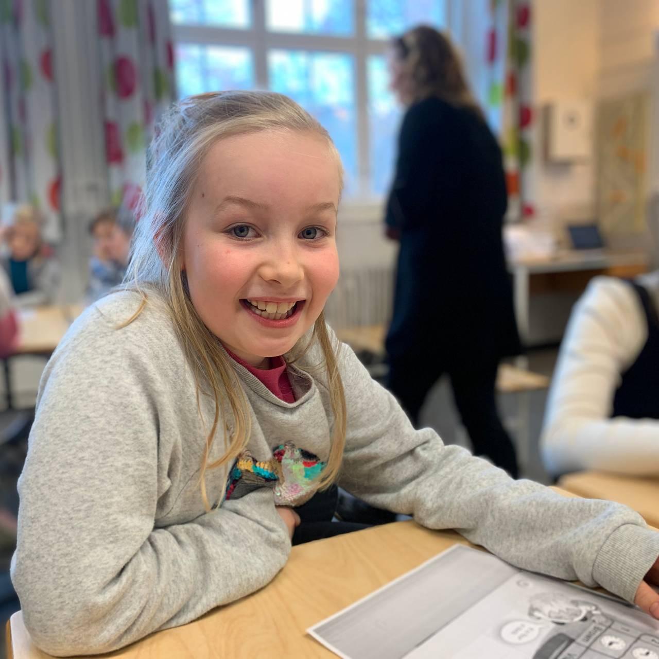 Hedvig sitter ved en pult i klasserommet.