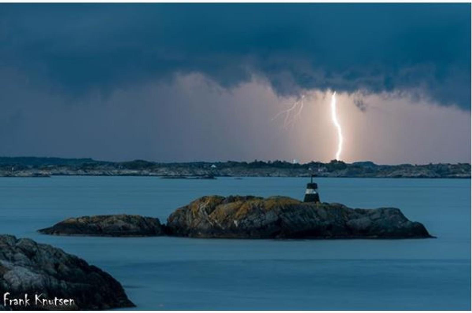 Holme i Homborsund med torden og lyn i bakgrunnen. - Fantastisk farger å se på god avstand, skriver fotografen som har delt bildet med @nrksørlandet på Instagram.