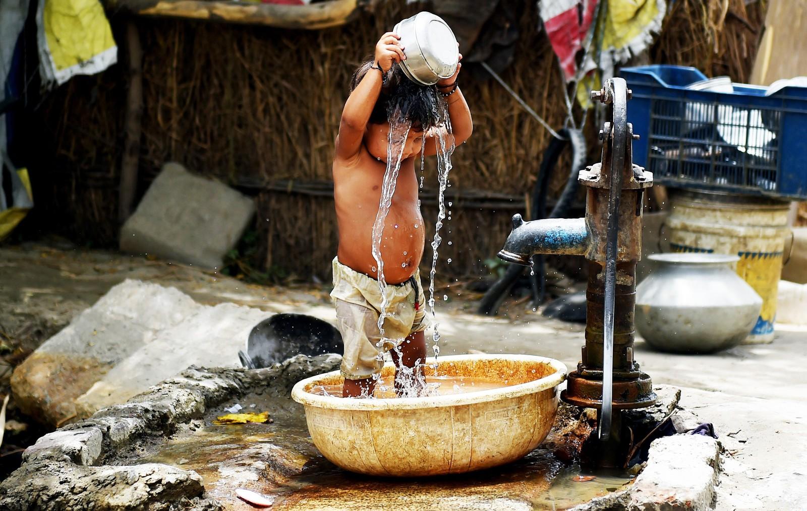 En liten indisk gutt forsøker å kjøle seg ned ved å helle vann fra en vannpost i New Delhi.