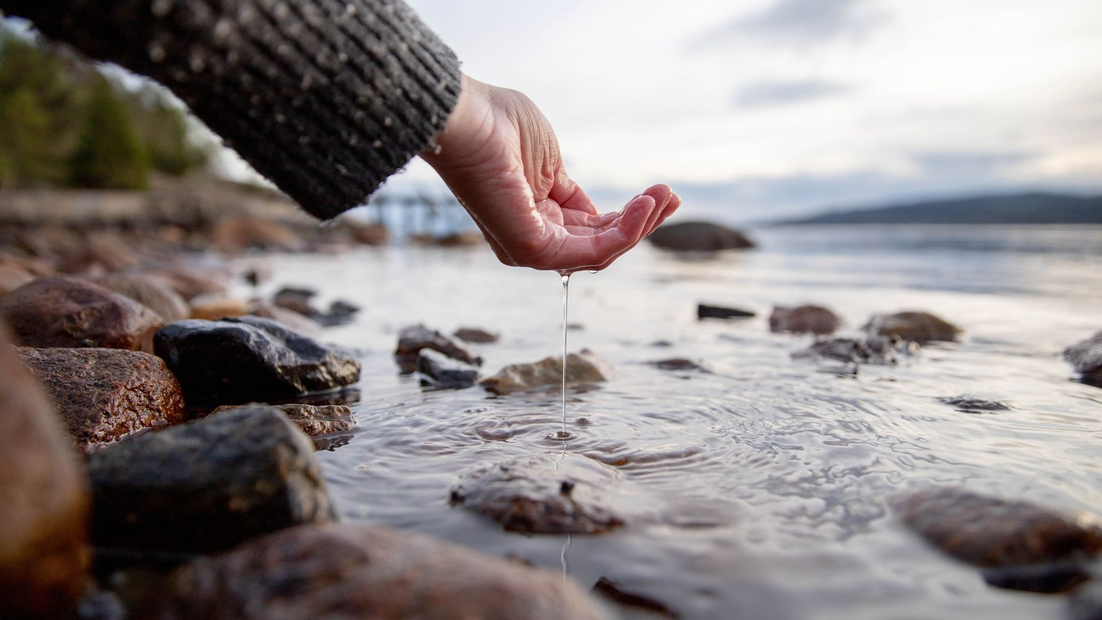 En arm i grå nuppete genser lar vann renne fra hånden ned i sjøen
