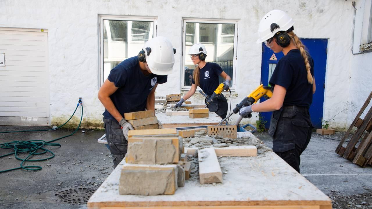 Tre sommervikarer står ute rundt et bord og arbeider med murstein. De to jentene bruker meisel og skrap for å rengjøre mursteinen. De har på hørselvern og vernebriller. Gutten til venstre stabler ferdig pusset stein. I forgrunnen ser man flere steiner som ikke er pusset ennå.