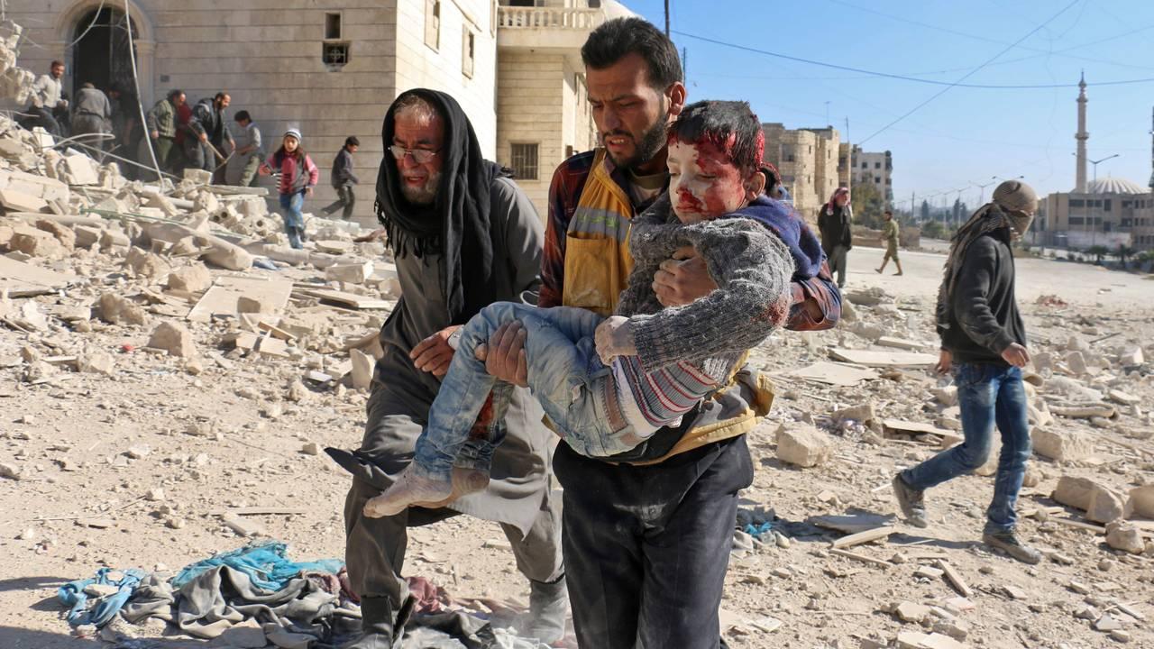 Et barn blir båret ut av ruinene etter et angivelig tønnebombeangrep i Aleppo.