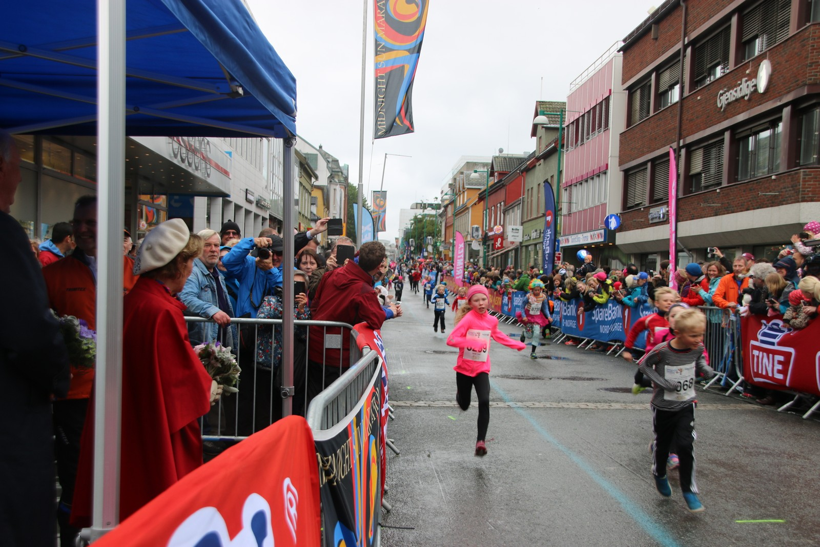 Kong Harald og Dronning Sonja tilstede under barneløpet i Midnight Sun Marathon i Tromsø lørdag, første stopp på jubileumsreisen som er en markering av kongeparets 25-årsjubileum. Foto: Ida Louise Rostad / NRK