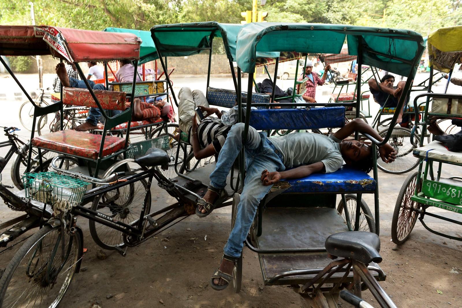 Rickshaw-førere tar seg en middagshvil i New Delhi.