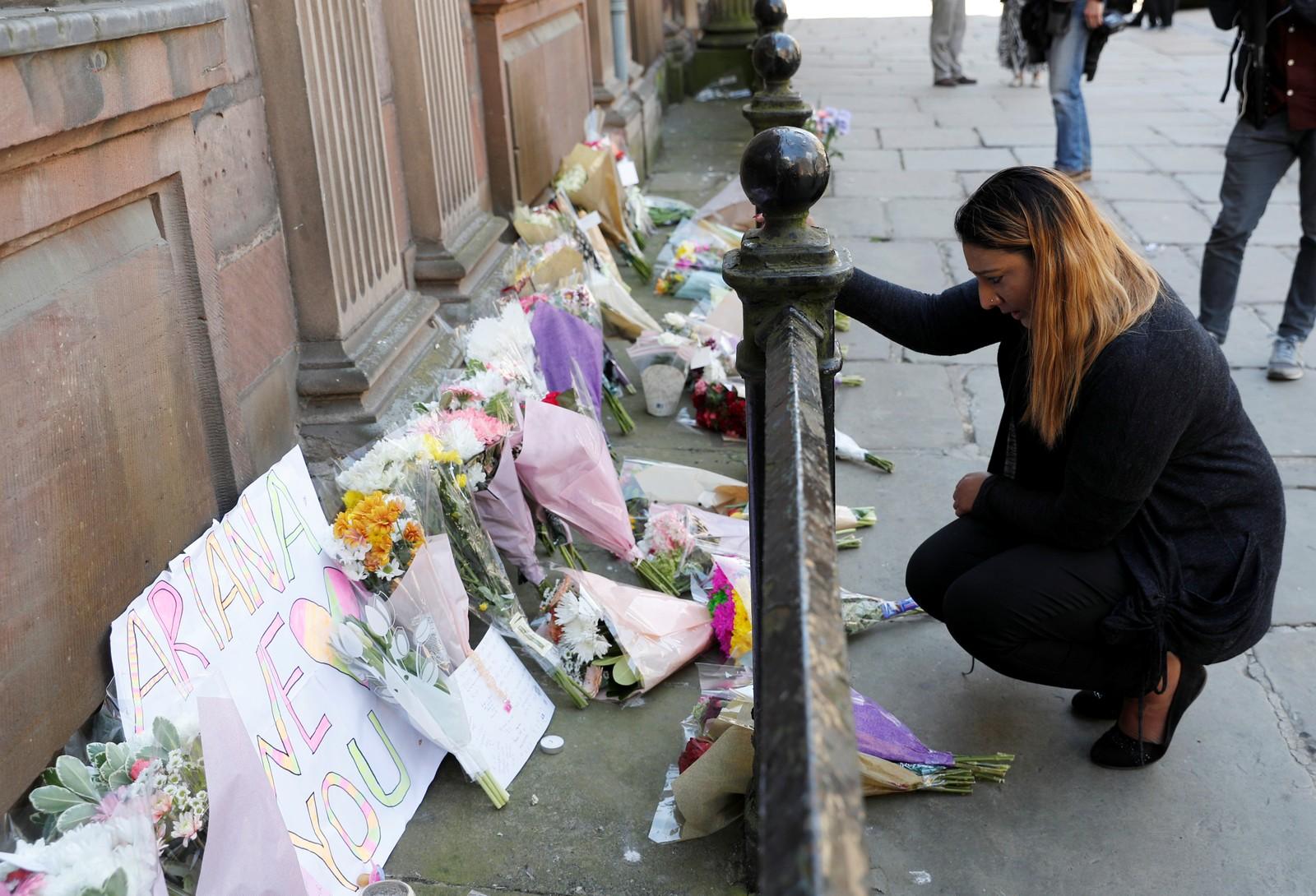En kvinne legger ned blomster for å minnes ofrene.