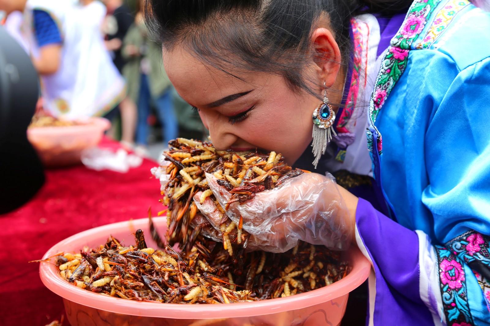 En kvinne gir alt under en spisekonkurranse i Lijang i Kina. Lekre insekter sto på menyen.