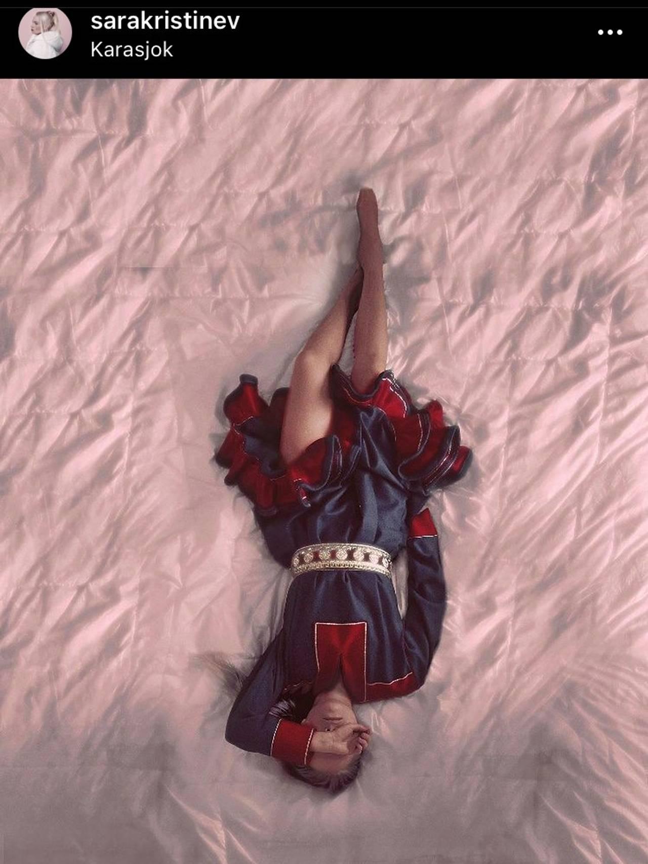 Sara Kristine Vuolab i kofte ligger på et laken med kofta på. Armen er slengt over ansiktet som om hun har det vondt.