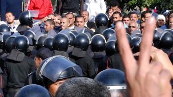 Demonstrant viser V-tegnet foran politi i Suez