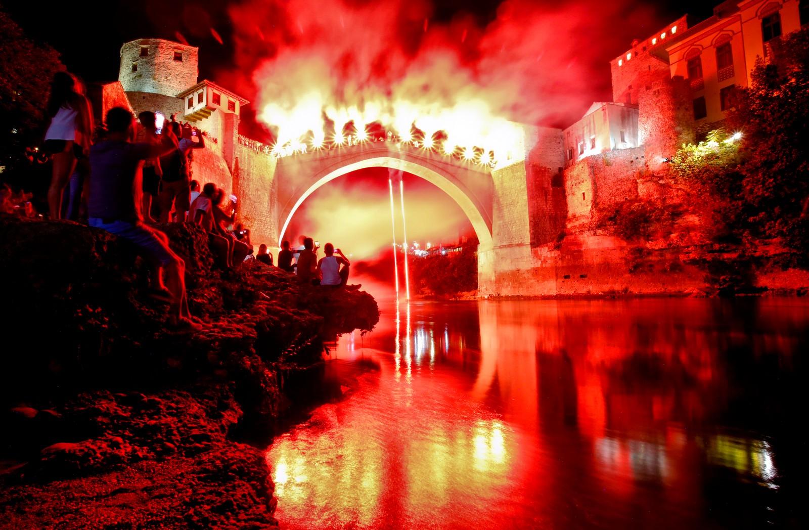 Her har fotografen brukt lang lukkertid. En stuper hopper i elven Neretva i Mostar i Bosnia mens han holder fakler i hendene. Over 10.000 mennesker var tilskuere mens 41 stupere viste sine kunster fra den 27 meter høye broen. Den årlige konkurransen har blitt holdt i nesten 500 år.