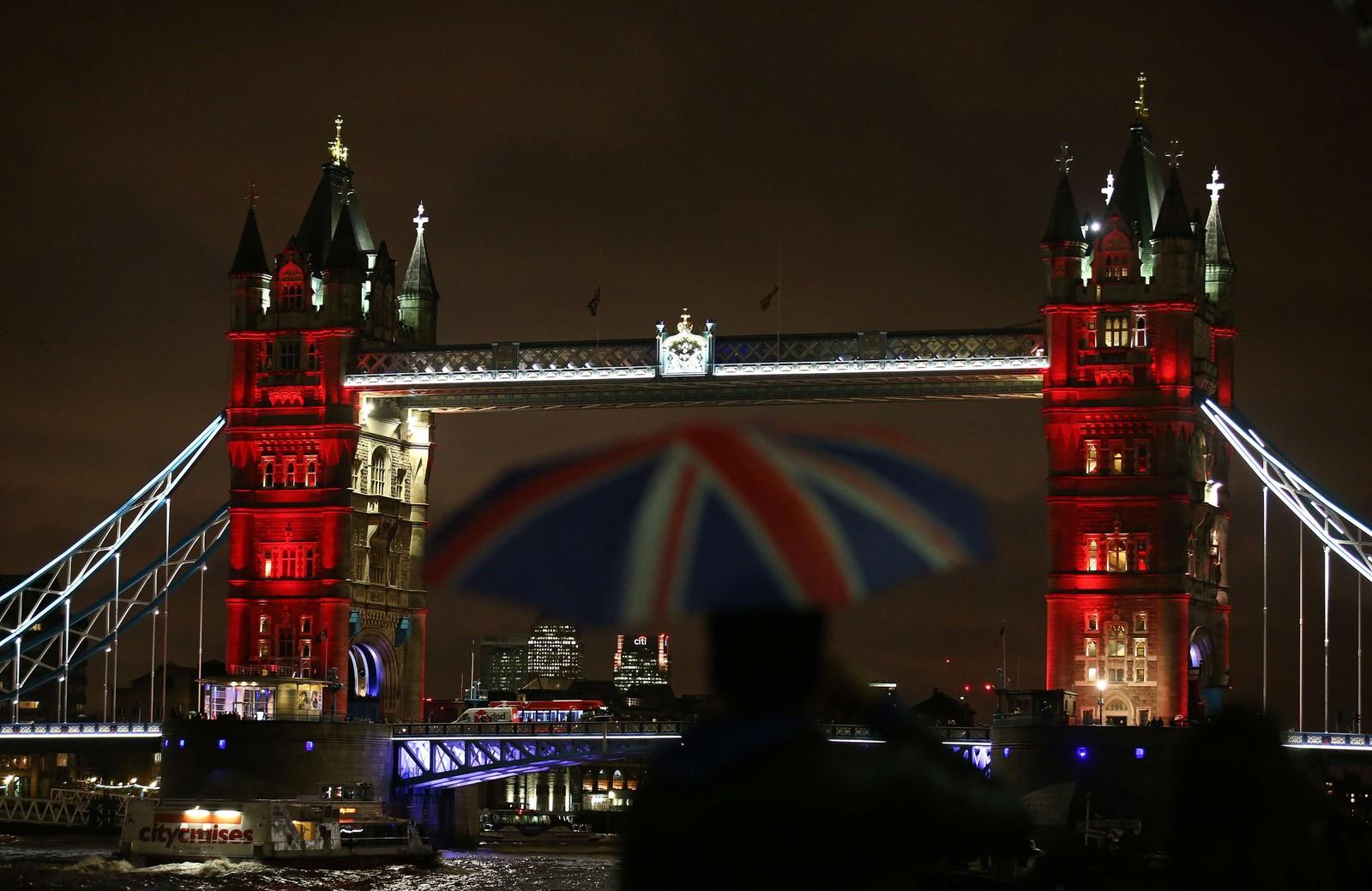 En mann beskytter seg fra regnet med en paraply i det britiske flagget. Bak ham lyses Londons ikoniske «Tower Bridge» opp i Frankrikes farger.