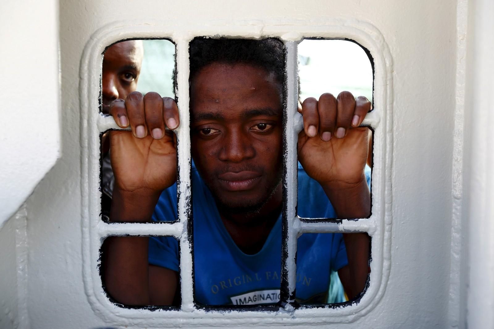 En flyktning titter ut av vinduet på Leger Uten Grensers redningsbåt Bourbon Argos idet den ankommer Trapani på Sicilia.