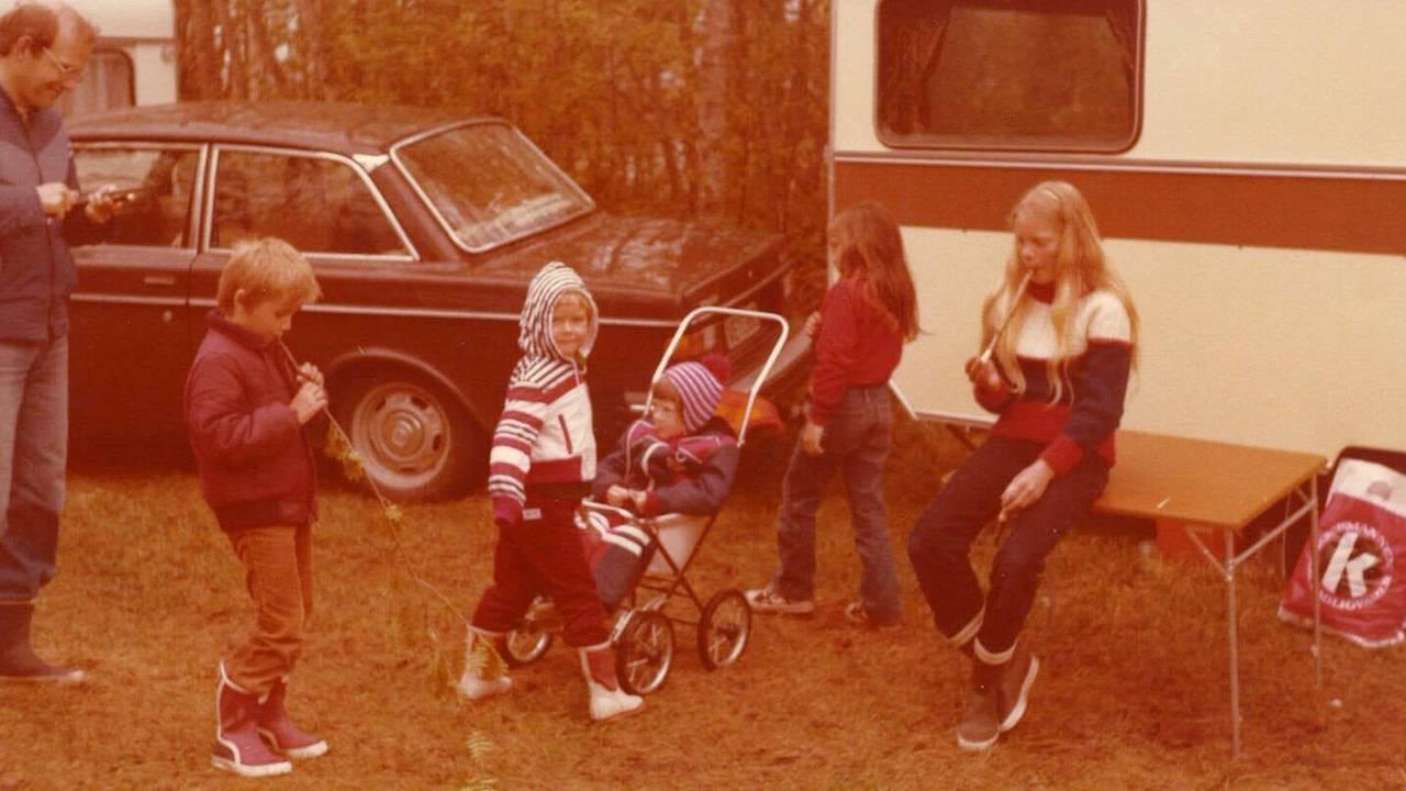 Eva Helen Angvik-Kristiansen sitter i vogn. Søsteren Anne Kathrine Angvik spiller blokkfløyte