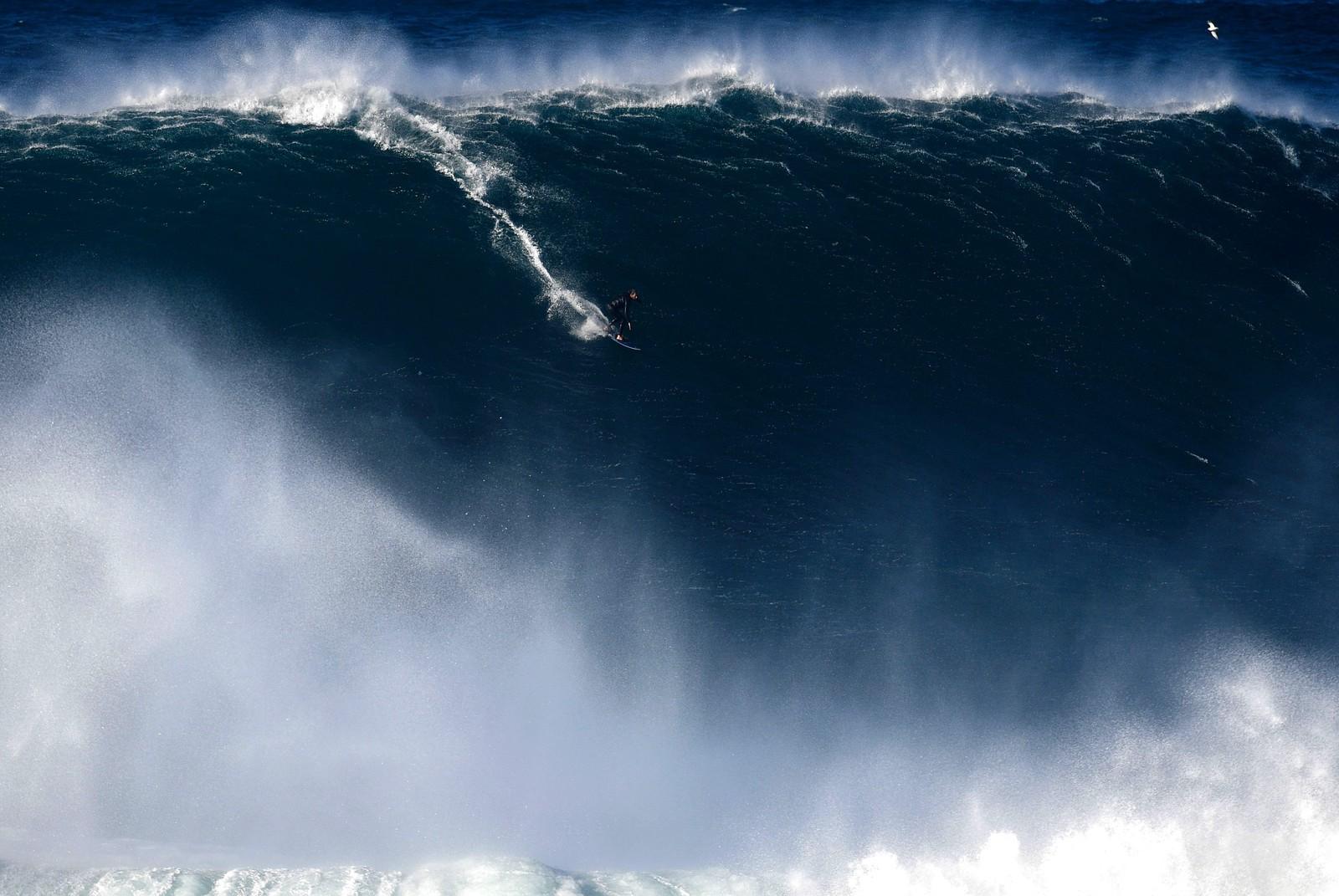 Han fant en bølge. Bildet av surferen er tatt ved Nazare i Portugal.