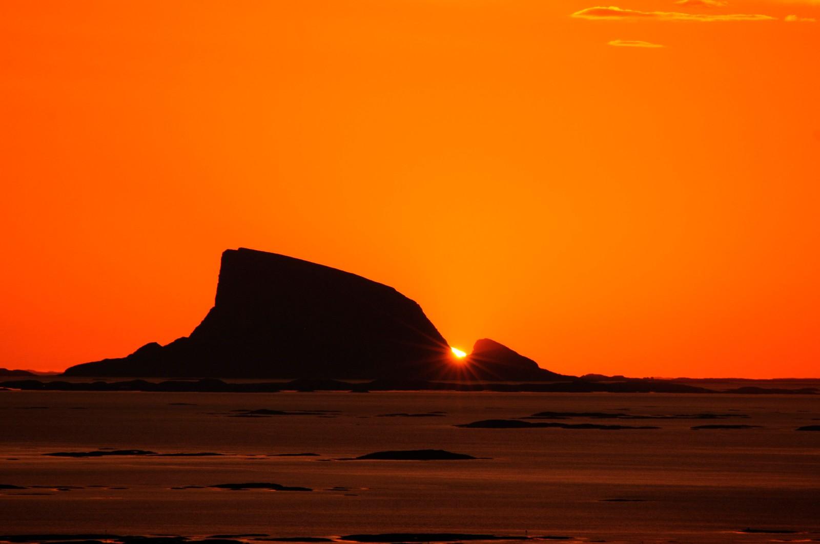 Sola går ned mellom to øyer på Helgelandskysten.