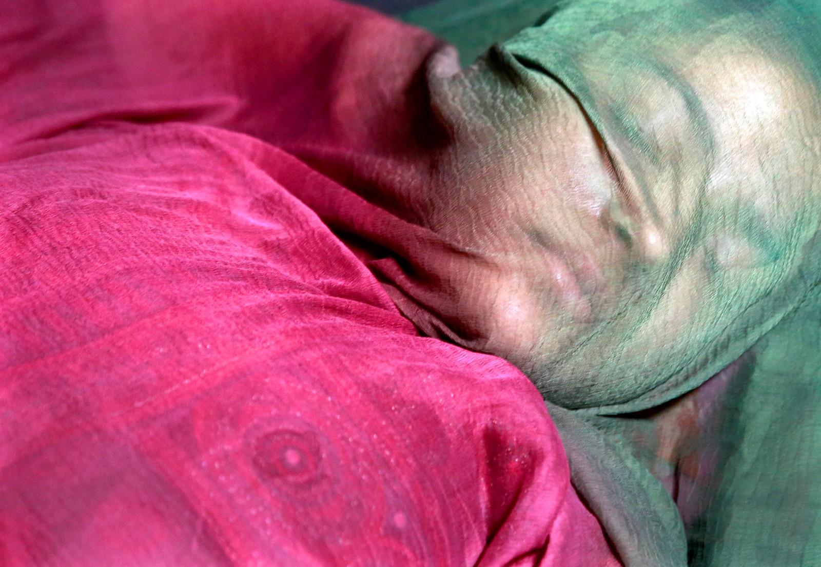 En jente sover bak en nedlagt butikk i Lucknow i India.