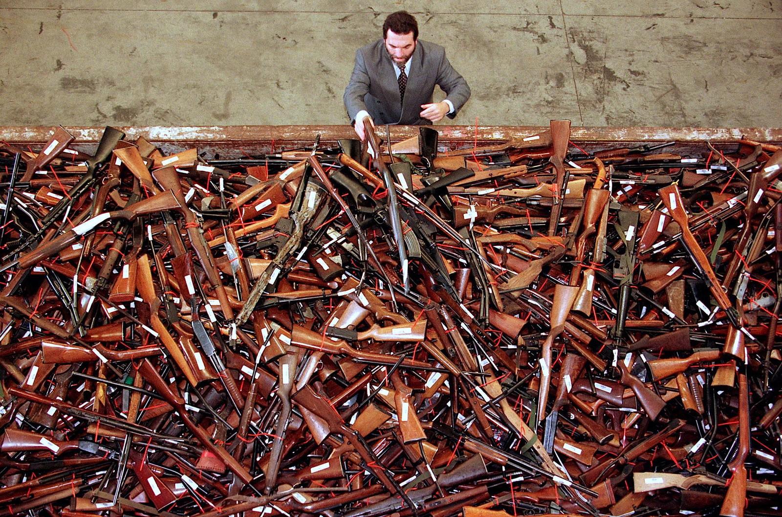 En representant for politiet i Sydney ser ut over et hav av våpen. 4.500 skytevåpen har blitt levert inn i bytte mot penger i forbindelse med de australske myndighetenes våpenamnesti.