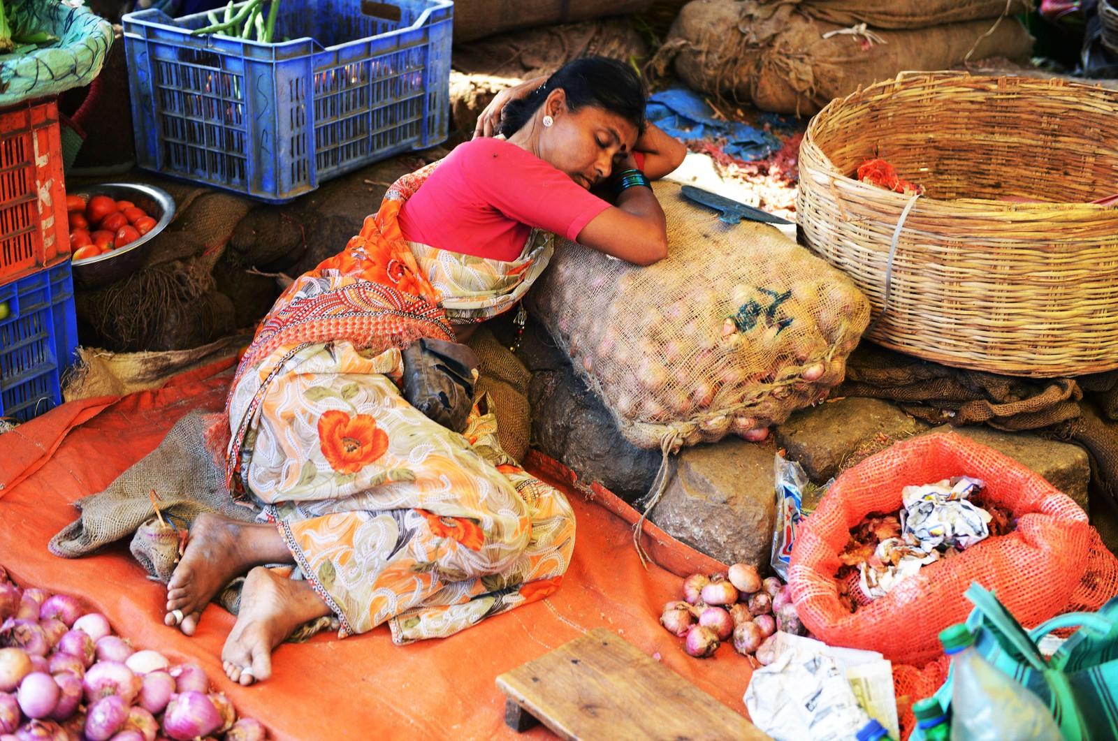 Kvinne sover på grønnsakmarkedet i Hyderabad i India.