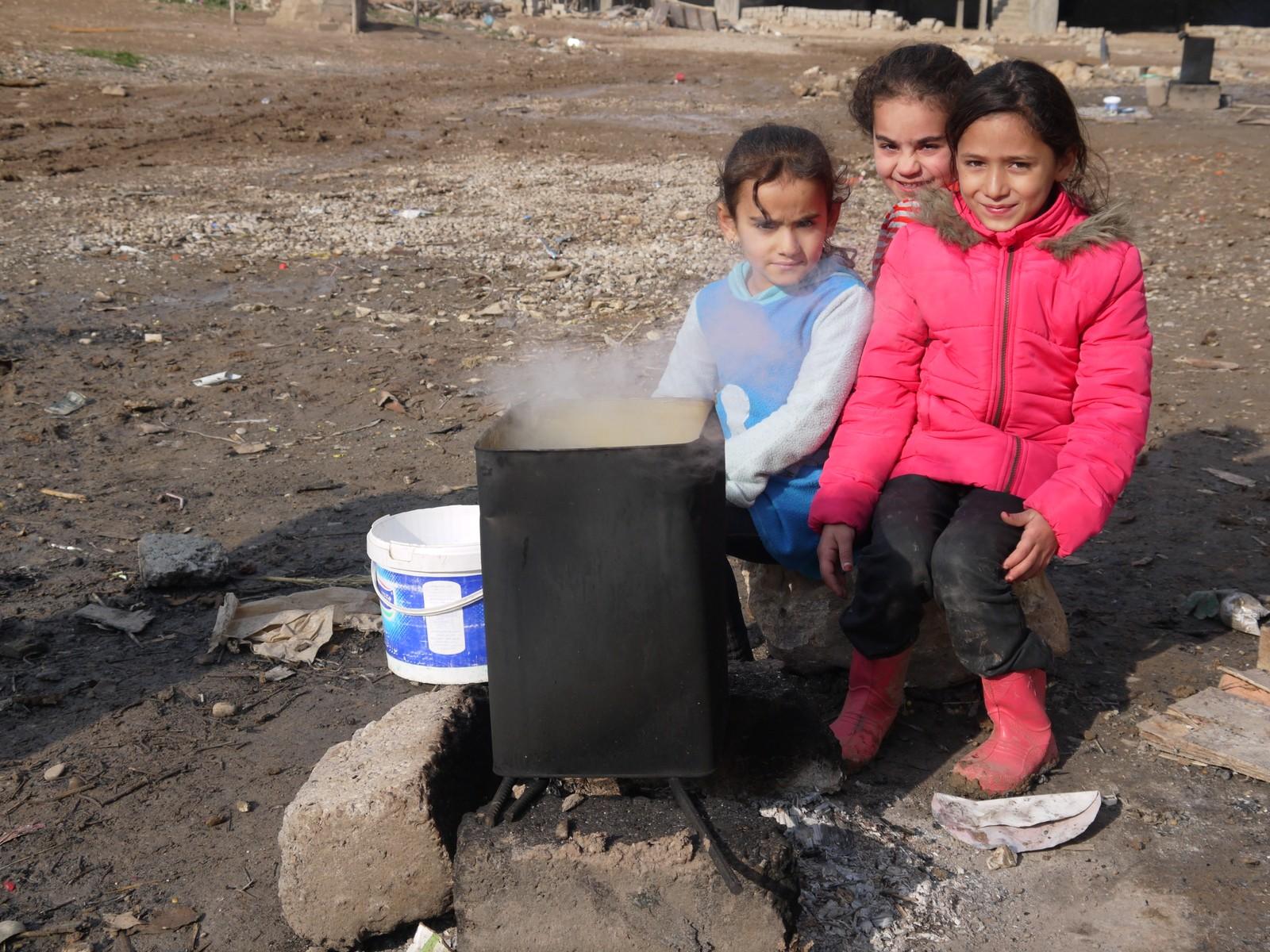 Det er kaldt i Irak. Tre jenter søker varme ved ein omn som står i ein av flyktningleirane utanfor Dohuk.