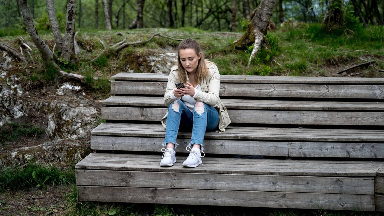 Bilde av Ingebjørg som sitter på en trappeaktig benk i skogen