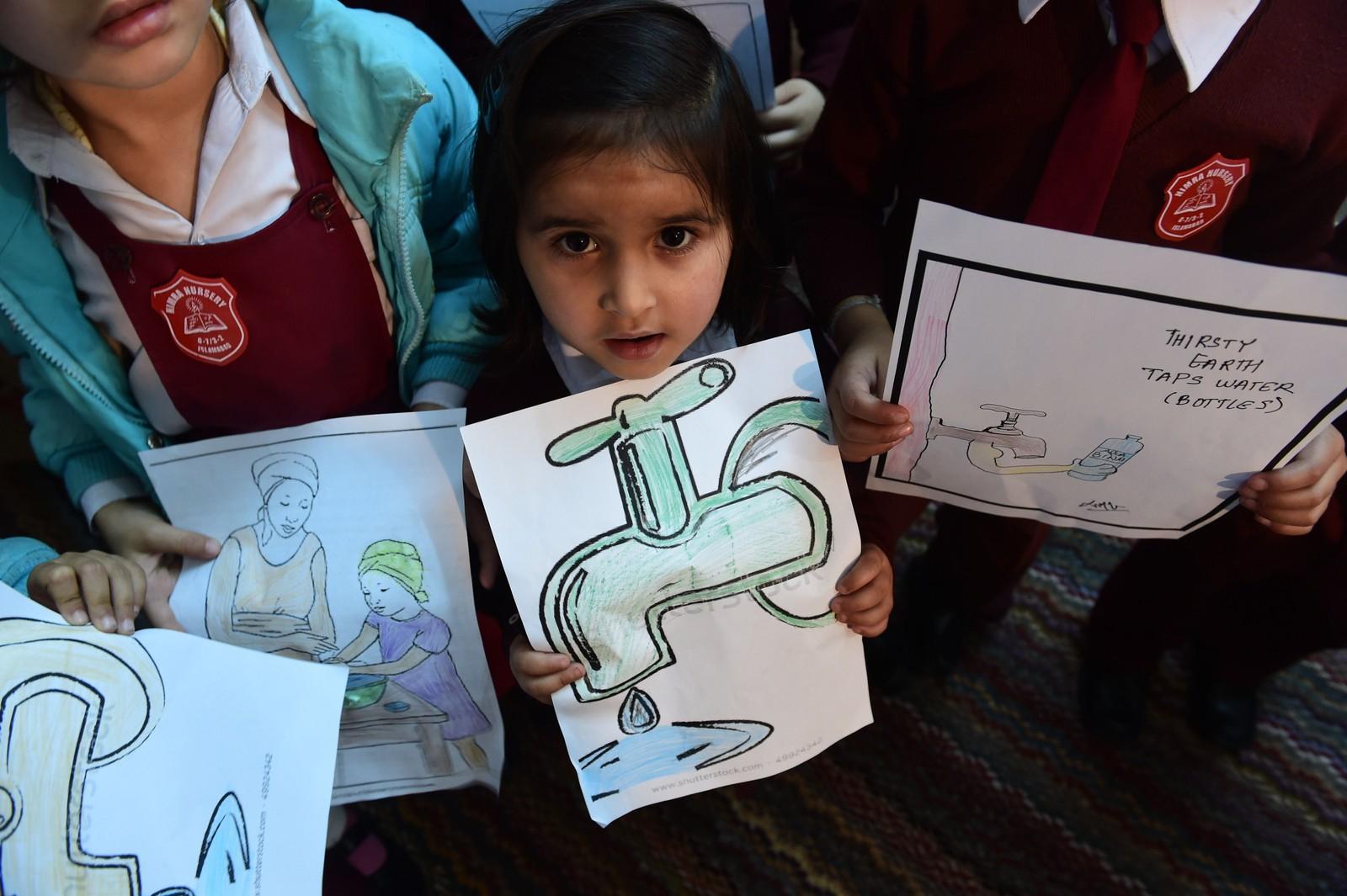 Pakistanske barn viser frem tegninger de har laget i forbindelse med verdens vanndag 22. mars.