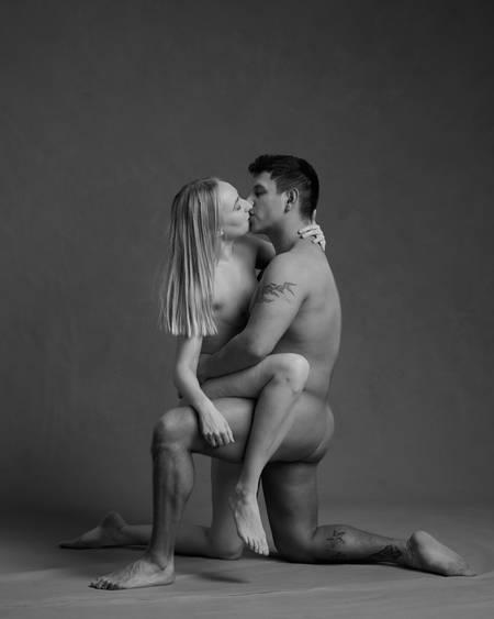 En naken kvinne med lyst hår og en naken mann med mørkt hår og tatoveringer sitter med ett ben på gulvet og det andre over kneet til hverandre mens de kysser