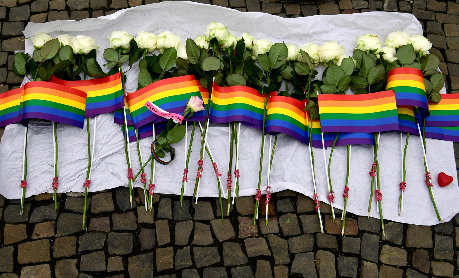 TYSKLAND: Det ble lagt igjen blomster og regnbueflagg utenfor den amerikanske ambassaden i Berlin mandag.