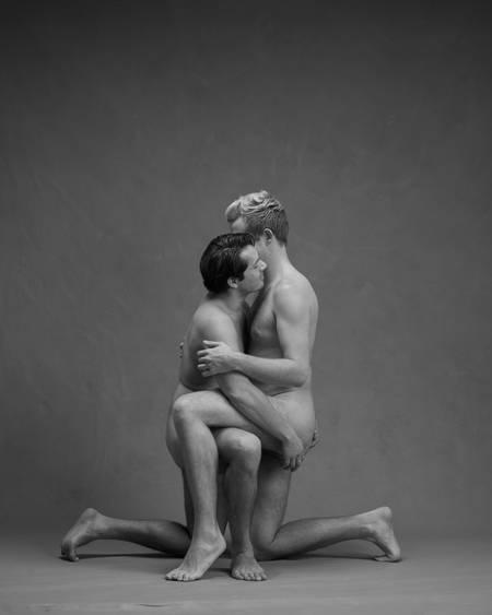 To nakne menn sitter med det ene benet å gulvet og det andre over hverandres lår mens de holder rundt hverandre