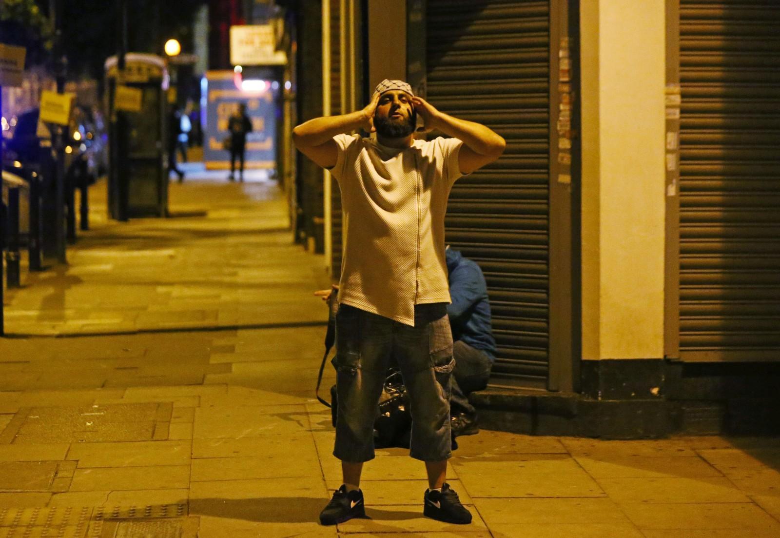 En mann ber en bønn etter at angrepet skjedde.