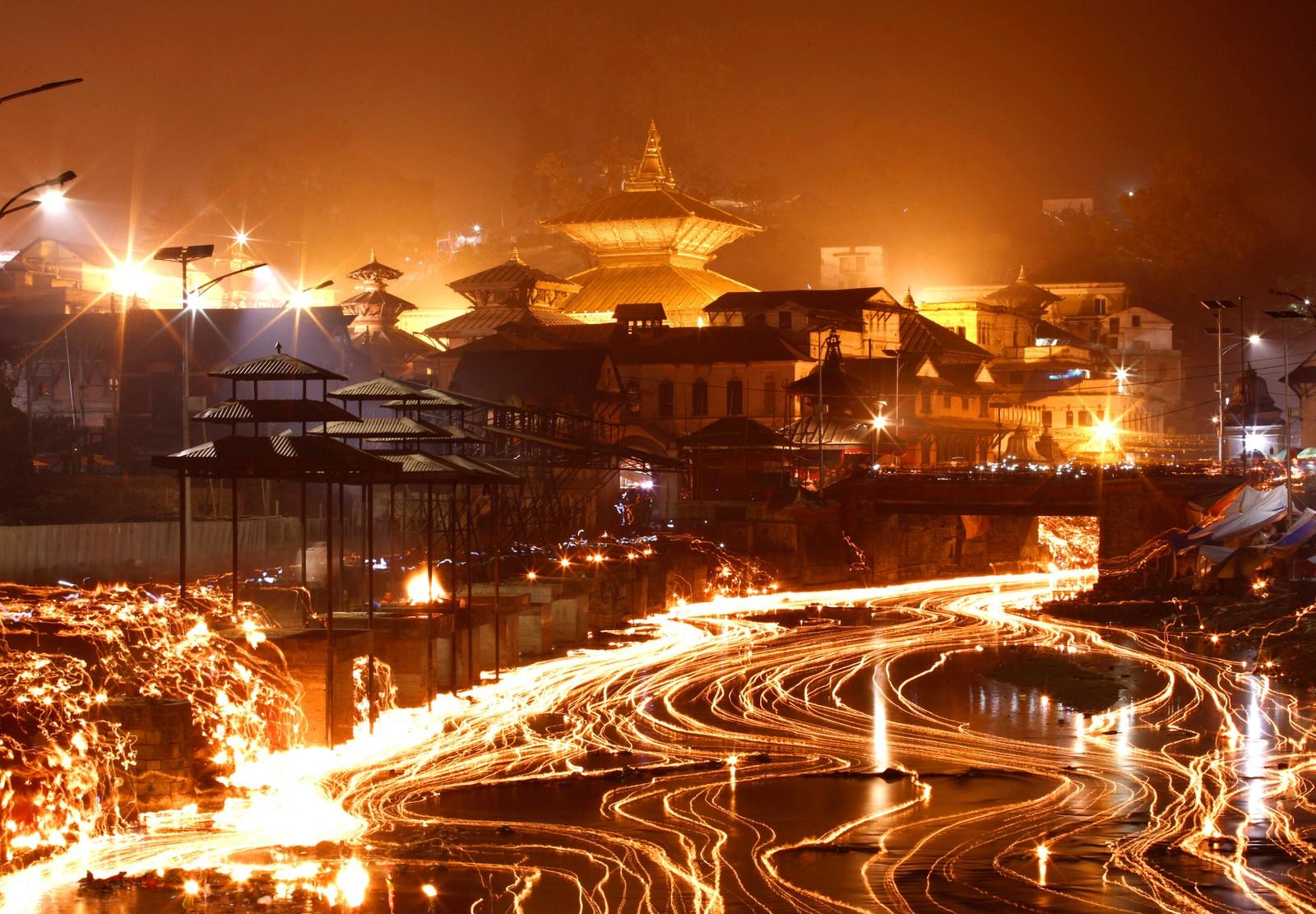 Oljelamper lyste opp elven Bagmati ved tempelet Pashupatinath under Bala Chaturdashi-festivalen i Katmandu i Nepal.