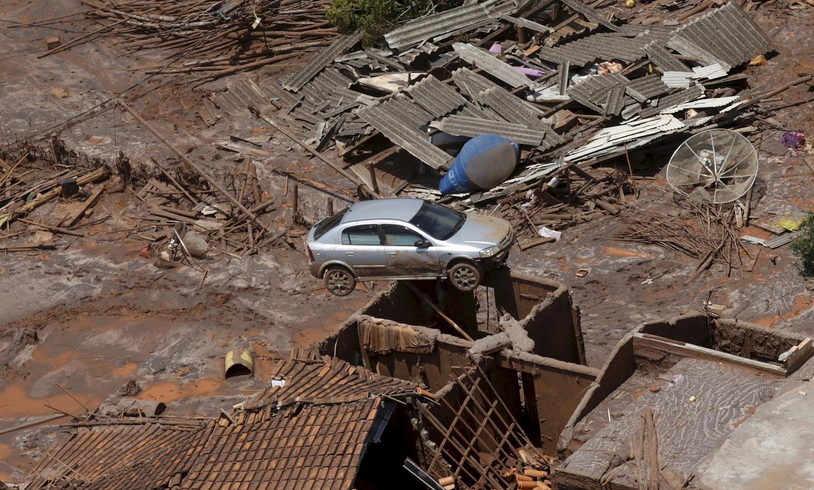 En bil henger nesten i løse luften i Bento Rodigues i Brasil, som ble dekket av gjørme etter at en demning kollapset i mars.