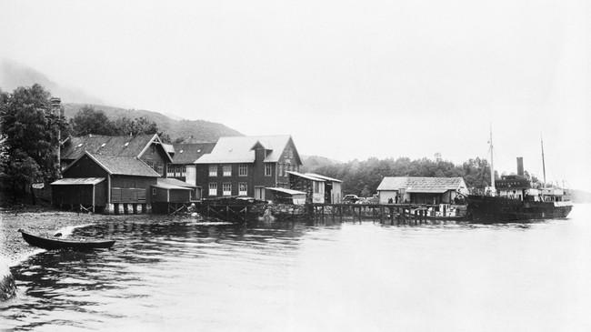 """Dampskipskaia i Dale på slutten av 1930-talet. DS """"Framnæs"""" ligg ved kai. Til venstre i biletet ligg skofabrikken. Ukjend fotograf. © Fylkesarkivet."""